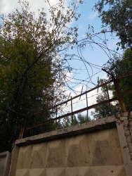 An old high concrete fence, supplemented with several rows of barbed wire on top. The silhouette of a protective fence made of metal barbed wire stands out clearly against the sky.
