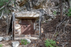 An old historic stone and steel safe with rusty locked door built into the side of a mountain in the 1800s in Great Basin National Park, Nevada