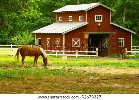 An old horse barn with a horse eating straw in the field in front of it