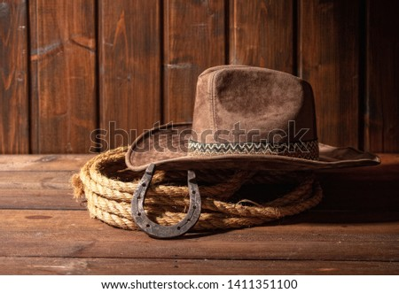 An old horseshoe lies next to a classic cowboy hat and lasso on a dark wooden background. #1411351100