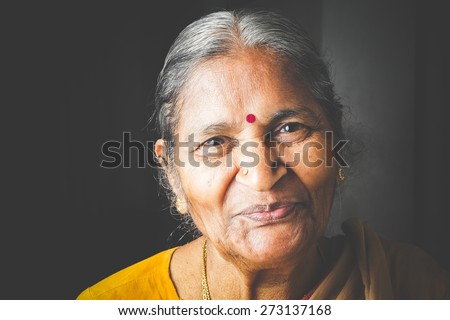 An Old Indian beautiful traditional woman smiling at he camera