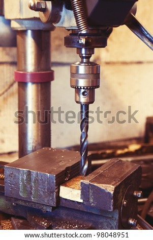 An old industrial electric heavy drill head in a factory for metal and wood drilling