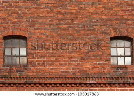 an old industrial wall made of red brick stones with two windows made of glass