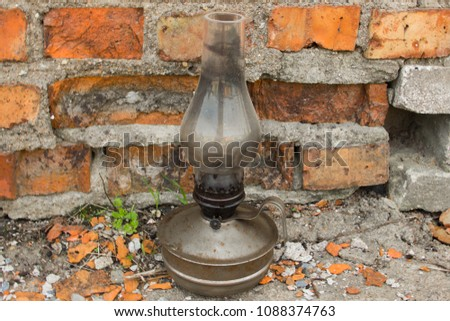 An old kerosene lamp. Old lamp. Kerosene lamp. Kerosene lamp on a background of red bricks. #1088374763