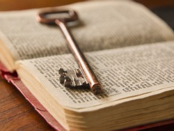 an old key on top of an old Bible