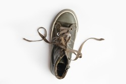 An Old khaki boy sneaker on white wooden background with curls from laces. sports shoes in a fun way