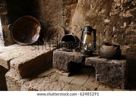 An old kitchen with pots, lamp and plate