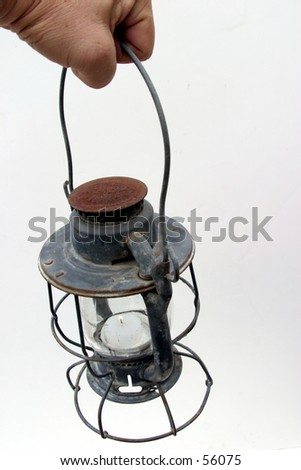 an old lantern with some rust and a lit candel inside being held by a real human hand against a white background