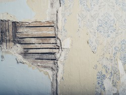 An old lath and plaster wall with antique wallpaper