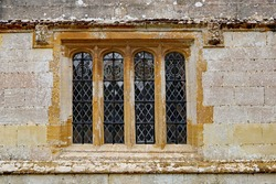 An old leaded window with a concrete frame in an old English country house