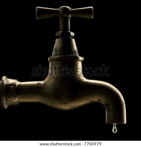 an old leaking tap against dark background