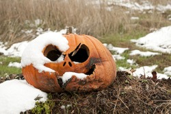 An old left over Halloween pumpkin rots outside in the cold snow in November