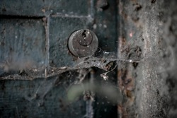 An old lock between dust and cobwebs.