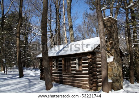 An old log cabin in the snow at Washington Crossing Park.