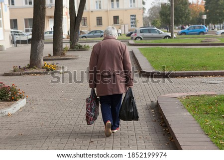 An old lonely elderly poor gray-haired woman with bags walks from the store or down the street. Rear view, face not visible. Foto stock ©
