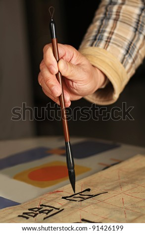 """An old man is practicing calligraphy using a brush pen in his leisure time. The Chinese words in the photo are : """"recognize the moon"""""""