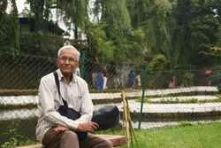 An old man is sitting on a bench in Lady Hydari Park at Shillong in Meghalaya, India. The man is wearing spectacles. Kipping bag and cap in hand he is looking towards the camera.