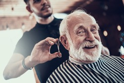 An old man looks at the camera while the master cuts his hair in a barbershop. An adult sidoy dede looks at the camera while he gets a stylish haircut.