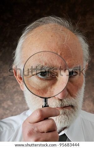 an old man sees through in magnifying lens in studio