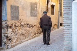 An old man walking alone in the narrow streets of Toledo, Spain