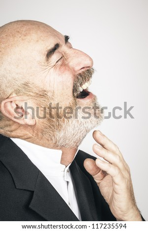 An old man with a grey beard is laughing