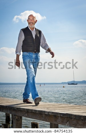 An old man with a grey beard is walking on a jetty - stock photo
