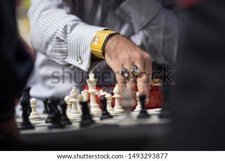 An old man with large rings playing multiple games of chess at the same time to entertain a crowd