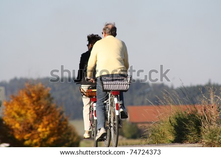 An old married couple ride with bicycle