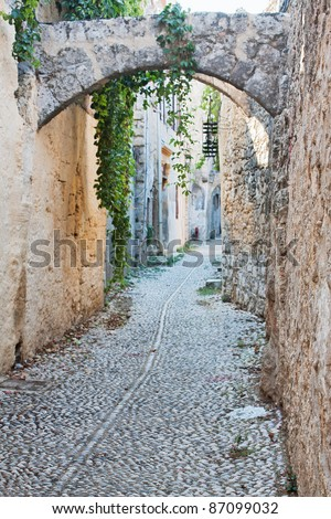 An old medieval cobblestone alley in Rhodes Old Town (a UNESCO World Heritage Site), Greece, with arches and stone facades.