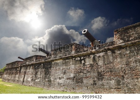 An old medieval fortress wall with ancient cannons guarding its sentry under a dramatic apocalyptic sky.
