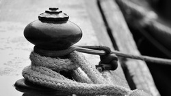 An old metal bollard photographed on a pier with heavy rope.  Presented in black and white.