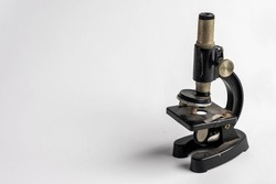 An old miniature microscope in a white background. Copy space of an miniature microscope.