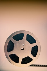 An old 16mm reel with film lies a brown background. For design.
