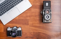 An old 35mm reflex camera, and an old medium format twin lens reflex camera, seen from above with a modern laptop next to them, horizontal