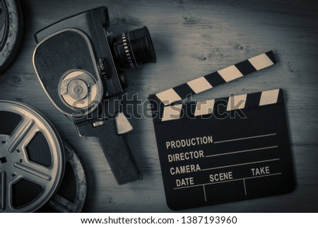 An old movie camera, movie reels and a clapperboard lie on a wooden board. View from above #1387193960