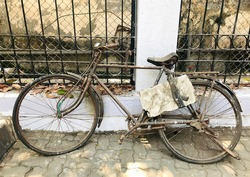 An old, much used vintage bicycle with a flat tyre and rusty body frame thrown on the sidewalk in Mumbai totally neglected.