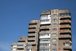An old multi-storey building of the Soviet era. A rundown, outdated, emergency building against a blue sky.