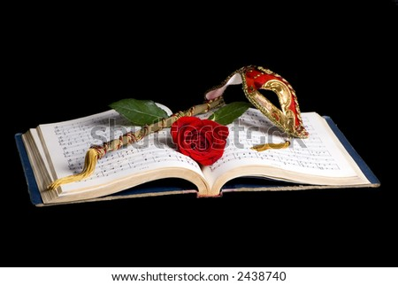 An old music book lays open with a mask and a single red rose on top.