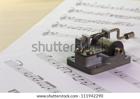 an old music box with note sheets on a desk