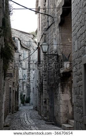 An old narrow street is in Croatia, city Trogir.