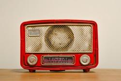 An old nostalgic red radio. Vintage radio on a table.