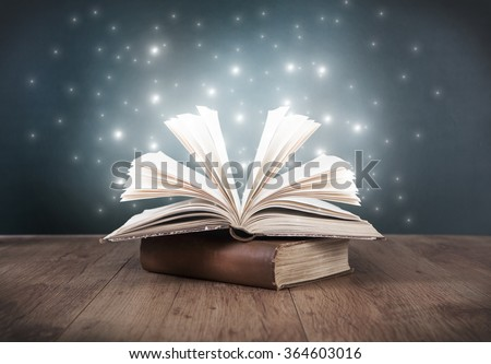 an old open book on a table in front of a blackboard Stock foto ©