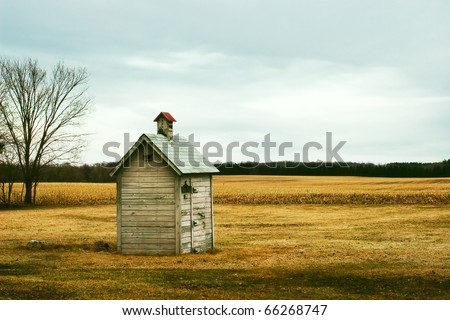 An old outhouse in the middle of an autumn field.