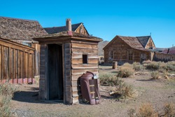 An old outhouse is a class hotrod grill leaned up against it in Bodie, California, USA.