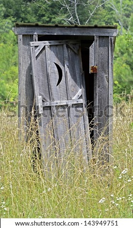 An old outhouse with door falling off surrounded by weeds.
