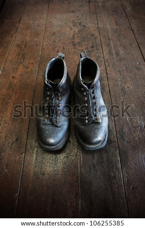 an old pair of leather boots on an old wooden floor