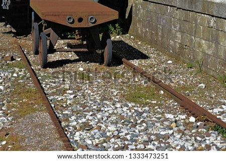 An old part of a train on tracks that seem abandoned