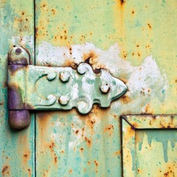 An old patterned hinge with rust decay