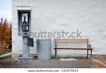 An old pay phone next to a metal trashcan and a wooden bench in front of a white painted cinderblock wall.