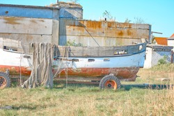 An old peeling fishing boat stands on the shore. A fishing net hangs on a boat. The texture of the old wood.